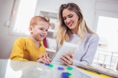 年轻母亲和她的儿子在孩子屋子里使用 免版税库存图片
