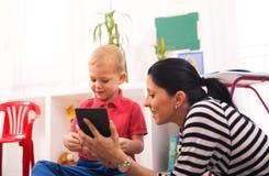 年轻母亲和她的儿子在孩子屋子里使用 库存照片