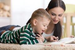 年轻母亲和她的儿童儿子在地板和阅读书上说谎 免版税库存图片