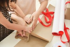 年轻母亲和她的包裹礼物盒的女儿手 免版税库存照片