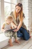年轻母亲和她的在家使用儿子的小孩 免版税库存图片