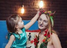 年轻母亲和她的女儿花梢服装的 免版税库存图片