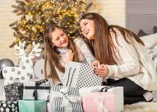 年轻母亲和她的打开不可思议的圣诞节的ittle女儿 库存图片