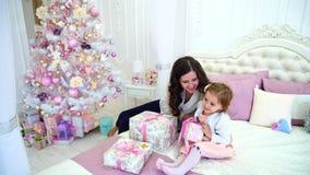 年轻母亲和小女儿为新年假日做准备在宽敞明亮的卧室坐床反对 影视素材
