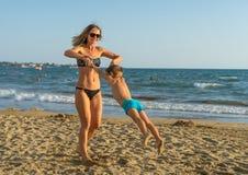 年轻母亲和微笑使用在天时间的海滩的男婴儿子 正面人的情感,感觉,喜悦 滑稽的逗人喜爱的池氏 免版税库存图片