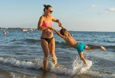 年轻母亲和微笑使用在天时间的海滩的男婴儿子 正面人的情感,感觉,喜悦 滑稽的逗人喜爱的池氏 库存照片