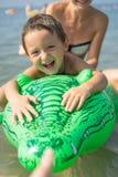 年轻母亲和微笑使用在天时间的海的绿色棒球帽的男婴儿子 正面人的情感,感觉, 免版税库存照片
