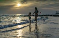 年轻母亲和微笑使用在日落的海滩的男婴儿子 正面人的情感,感觉,喜悦 儿童逗人喜爱滑稽 免版税图库摄影