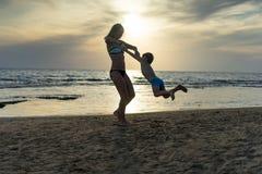 年轻母亲和微笑使用在日落的海滩的男婴儿子 正面人的情感,感觉,喜悦 儿童逗人喜爱滑稽 库存照片