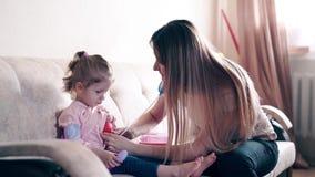 年轻母亲和甜女儿扮演医生和患者的角色 股票录像