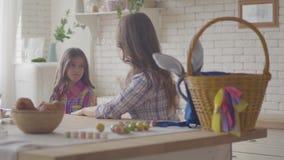 年轻母亲和逗人喜爱的女儿谈话在厨房 听她的情感女孩的妇女,爱抚她的头发和 股票录像