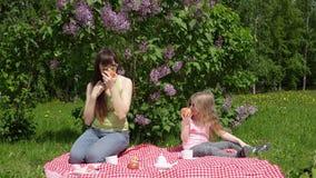 年轻母亲和litlle女儿春天的在开花的丁香旁边去野餐 股票录像