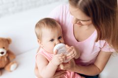 年轻母亲哺养的婴孩牛奶瓶家 免版税库存照片