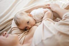 年轻母亲在她的胳膊哺乳她的女婴,拿着她和微笑从幸福 9个月大孩子 库存照片