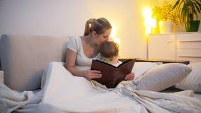 年轻母亲在床上的亲吻她的小孩儿子阅读书在晚上 免版税库存图片