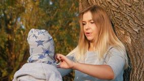 年轻母亲坐与她的小婴孩的草,拿着他 修理他的衣裳 股票视频