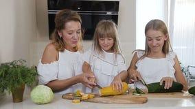 年轻母亲显示孩子如何在家砍菜在厨房里 少妇和她的两个女儿切开 股票视频