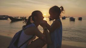 年轻母亲柔和的画象有她的小女儿的在日落的海滩的 股票视频