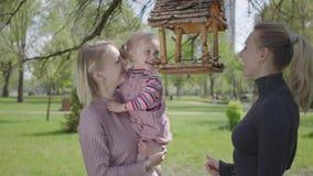 年轻母亲消费时间在有她的女儿的公园 举她的女孩,因此她的妇女可能看鸟 股票视频