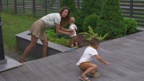 年轻母亲演奏和获得与她的男婴儿子兄弟的乐趣在有玩具的一个庭院-家庭价值观温暖的颜色里 影视素材