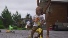 年轻母亲演奏和获得与她的男婴儿子兄弟的乐趣在有自行车的一个绿色庭院里-温暖的家庭价值观 股票视频