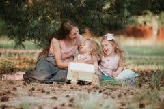 年轻母亲照片有两个户外逗人喜爱的孩子看书的在春天,幸福家庭,母亲节概念 免版税库存图片