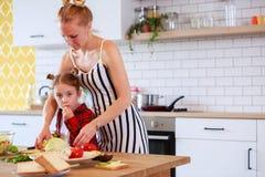 年轻母亲的图片有她的女儿切口菜的在厨房里 免版税库存照片