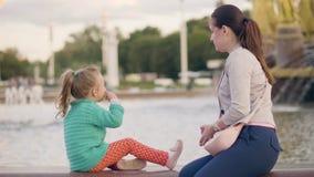 年轻母亲togerher一点女儿在喷泉水中的把硬币扔出去在公园 股票视频