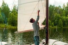 年轻水手培养在一艘小航行的筏的风帆 免版税库存照片