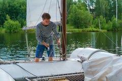 年轻水手培养在一艘小航行的筏的风帆 免版税图库摄影