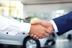 年轻汽车推销员与客户握手在经销权中 库存图片