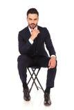 年轻沉思商人坐椅子 免版税库存图片