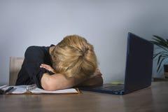 年轻沮丧和被注重的女商人哭泣哀伤在办公桌与文书工作workl淹没的便携式计算机一起使用 库存图片
