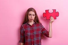 年轻沮丧的女孩、举行一个大红色难题和鬼脸 在桃红色背景 免版税库存图片