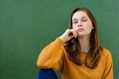 年轻沮丧的女性高中学生在黑板前面在教室,用她的手坐下巴 免版税库存图片