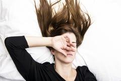 年轻沮丧的妇女在她的床上在,盖她的面孔用她的手 免版税图库摄影