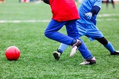 年轻活跃控和踢在橄榄球场的红色和蓝色运动服的体育石南丛生的男孩一个红色球与人为草皮 库存图片