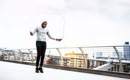 年轻活跃黑人运动员跳与一条绳索的在城市,佩带的有冠乌鸦 免版税库存图片