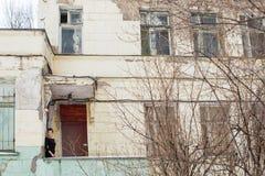 年轻浅黑肤色的男人冬天画象一家被放弃的医院的墙壁的背景的 免版税库存照片