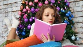 年轻浅黑肤色的男人在一棵典雅的圣诞树的背景读一本书 非常规的颜色,创造性 股票视频