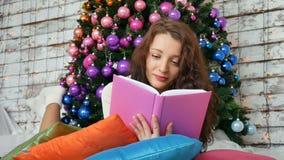 年轻浅黑肤色的男人在一棵典雅的圣诞树的背景读一本书 非常规的颜色,创造性 股票录像