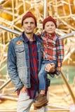 年轻浅黑肤色的男人照片有她的儿子的在铁结构附近在秋天公园 库存图片