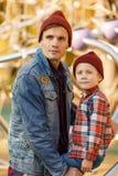年轻浅黑肤色的男人的图象有他的儿子的在铁结构附近在秋天公园 库存图片