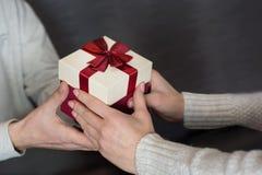 年轻浪漫夫妇坐给礼物盒的餐馆桌和人年轻女性手 免版税库存照片