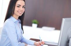 年轻深色的女商人看起来工作在办公室的学生女孩 西班牙或拉丁美洲的女孩愉快在工作 免版税库存照片