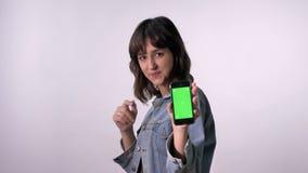 年轻深色的女孩在智能手机,移动,通信概念,白色背景绿色屏幕上指向  股票录像