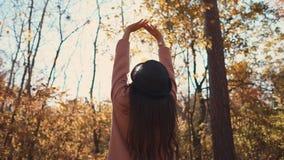 年轻深色的女孩在秋天森林和举的手,后面里单独站立 股票视频