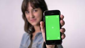 年轻深色的女孩显示智能手机绿色屏幕,观看在照相机,通信概念,白色背景 股票视频