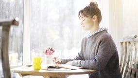 年轻深色的女孩档案读调查在咖啡馆的一个笔记本 免版税库存图片