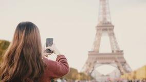 年轻深色的女性为照相的埃佛尔铁塔后面看法在智能手机的 探索巴黎,法国的少年 股票录像